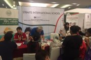Visitors at the Straits International School table