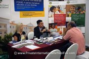 A parent getting information at the Prince of Wales Island International School table