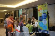Parents speaking with school representatives at the Fairview International School table