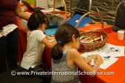 Children colouring at the Canadian International School table