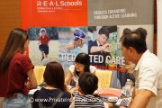 Parents getting information from the R.E.A.L Schools booth