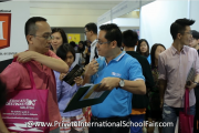 An I-MAX Financial representative explains to a visitor the cost of education