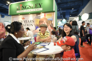 A family interacting with a representative from Kingsley International School