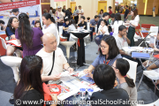 Visitors speaking to a GEMS International School representative