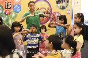 Kids learning a dance move from a Young Choral Academy representative